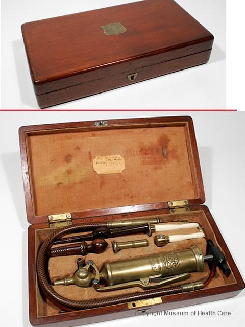 Pompe à estomac et lavement dans une boite en bois avec doublure de velours et contenant plusieurs accessoires en laiton, cuir et ivoire.