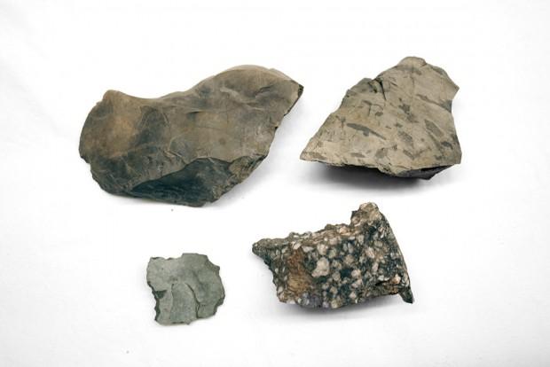 Quatre pierres grises, travaillé en différentes formes pour devenir des outils