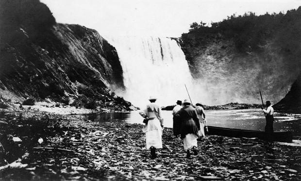 Épreuve argentique d'Elsie Reford et d'Evelyn MacInnes marchant sur les roches de la berge de la rivière Mitis, approchant du pied de la chute et sur le point d'embarquer dans leur canot pour une journée de pêche.