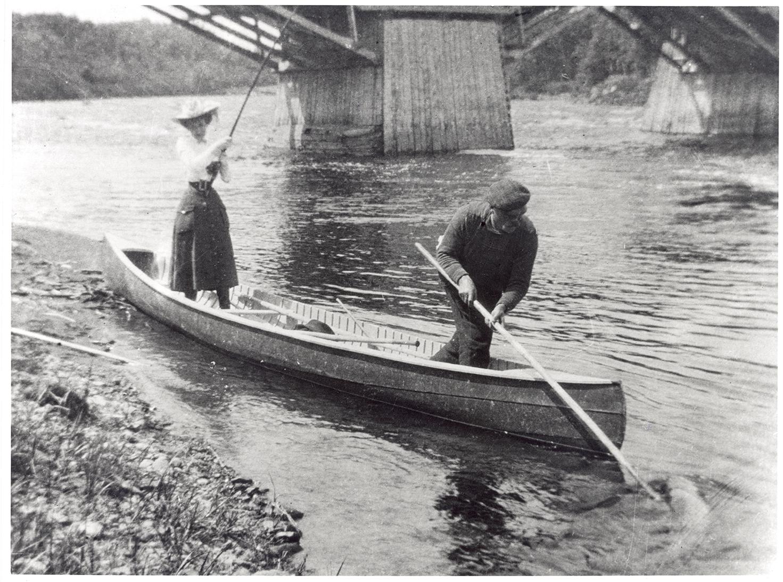 Épreuve argentique montrant Elsie Reford, debout dans un canot sur la berge de la rivière. Elle est vêtue d'une jupe mi-longue, une chemise blanche et d'un chapeau élégant. Elle semble tirer une longue canne à pêche. Un homme, situé au devant du canot sort un gros poissons de la rivière a l'aide d'une longue pôle et d'un crochet.