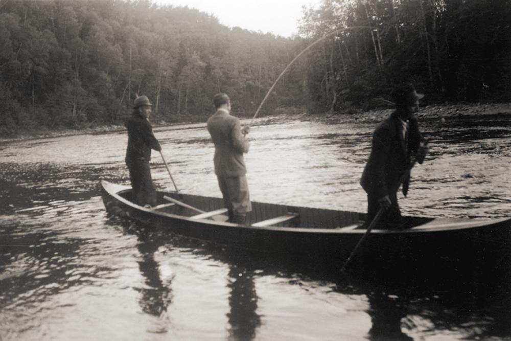 Lord Tweedsmuir pêchant debout dans un canot sur la rivière Mitis