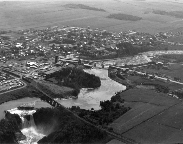 Cette photographie aérienne montre le village de Price au pic de sa prospérité. La compagnie de la Price Brothers occupait un large territoire voisin de la rivière. On retrouve aussi de chaque côté de la rivière les terminale de chemin de fer du Canada et du Golf.