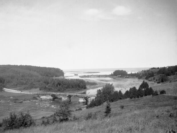 Vue de l'embouchure de la rivière Mitis sur laquelle on aperçois l'ancien pont de bois, les vestiges du quai de la Price Brothers company, une goelette et le mât du belvédère de la Villa Estevan.
