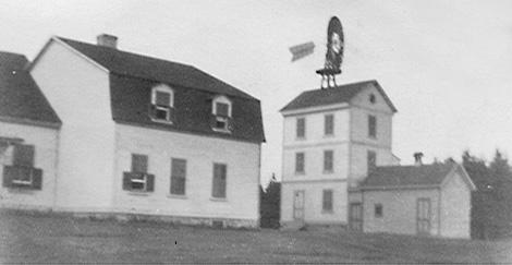 Épreuve argentique de l'arrière de la Villa Estevan montrant un bâtiment adjacent surmonté d'une éolienne.