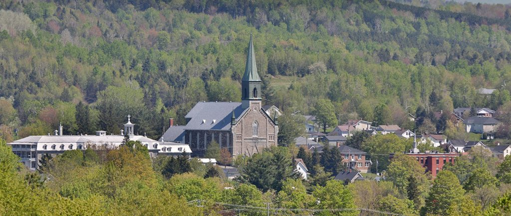 Photo couleur d'une vue partielle de Coaticook dans un paysage boisé. On peut voir l'Église St-Edmond avec son clocher, le grand bâtiment du Collège Rivier et d'autres bâtisses.