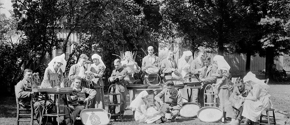 Photo en noir et blanc de soldats de la Première Guerre mondiale en convalescence, accompagnés de leurs infirmières. Ils sont à l'extérieur, par une journée ensoleillée, autour de tables avec des objets d'artisanat.