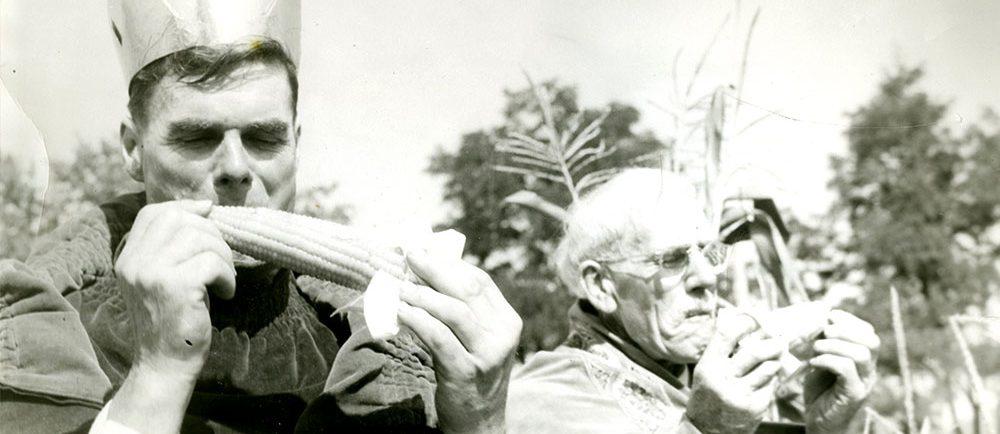 Photographie en noir et blanc de deux hommes vêtus d'une robe royale qui dégustent des épis de maïs : Norman Morrow, roi du maïs en 1950 est à gauche, et Sam Stock, roi du maïs en 1949 est à droite.