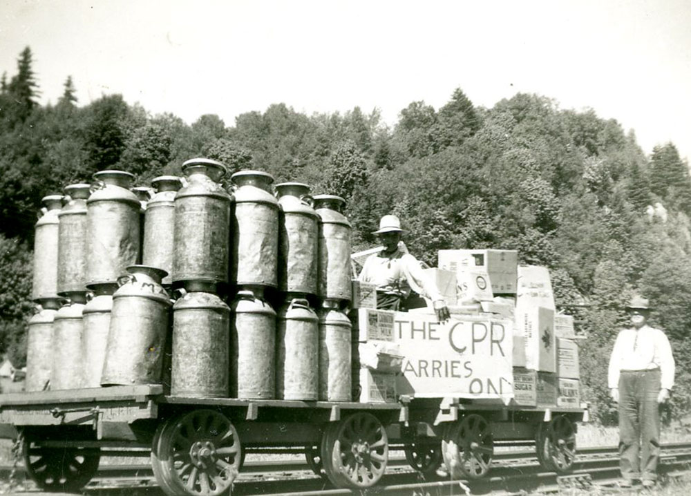 Photo en noir et blanc avec des bidons de lait sur un wagon plat surbaissé. Deux hommes tiennent une pancarte sur laquelle on peut lire « The CPR Carries On » (Le CFCP tient le coup).