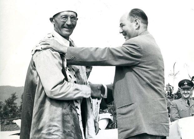 Photo en noir et blanc de deux hommes debout sur un podium qui se serrent la main. Un homme porte un manteau royal et une couronne tandis que l'autre porte un habit, 1954.