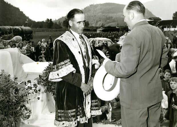 Photo en noir et blanc de deux hommes debout sur un podium. L'un porte un manteau royal alors que l'autre porte un habit et tient un chèque, 1953.