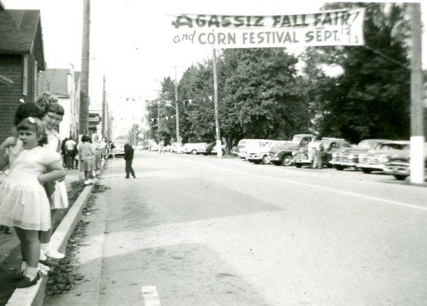 Photo en noir et blanc avec des gens rassemblés au bord d'une rue pour voir un défilé. Sur une bannière qui flotte au-dessus de la rue on peut lire : « Agassiz Fall Fair and Corn Festival », 12 et 13 septembre.