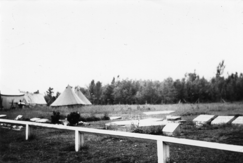 Photo en noir et blanc de tentes blanches à côté d'un cimetière.