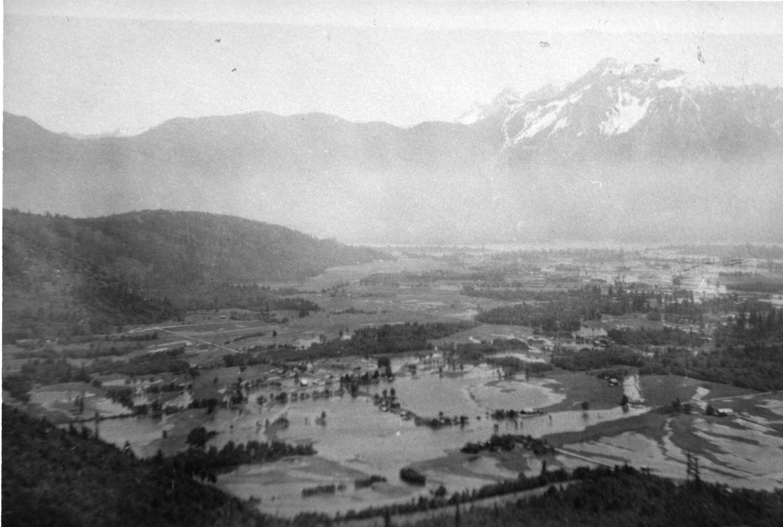 Photo en noir et blanc des champs inondés avec des montagnes en arrière-plan.