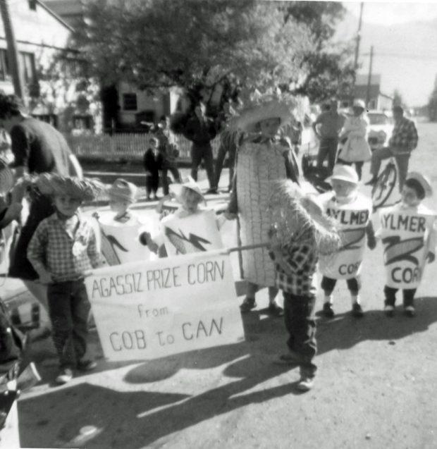 Photo en noir et blanc d'enfants dans un défilé, déguisés en épis de maïs et en boîtes de maïs. Deux enfants tiennent une pancarte sur laquelle il est écrit : « Agassiz prize corn from cob to can » (Le maïs primé d'Agassiz, de l'épi à la boîte).