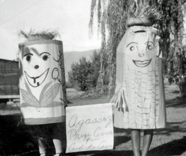 Photo en noir et blanc de deux personnes déguisées en épis et en boîtes de maïs. Ils tiennent une pancarte sur laquelle il est écrit : « Agassiz prize corn from cob to can » (Le maïs primé d'Agassiz, de l'épi à la boîte).