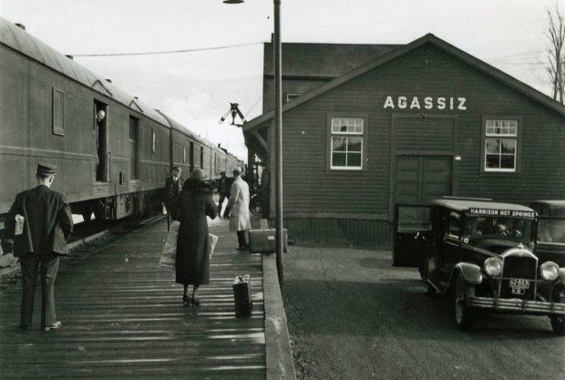 Photo en noir et blanc d'un train à la gare d'Agassiz où des passagers attendent sur un quai. Un taxi de Harrison Hot Springs est au premier plan.