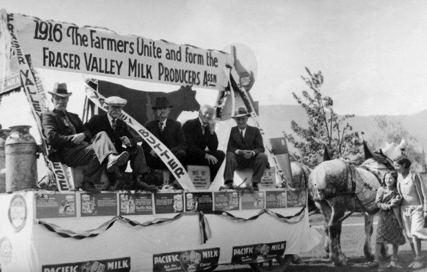 Photo en noir et blanc de cinq hommes sur un char allégorique tiré par un attelage de chevaux. Il y a une enseigne sur le char sur laquelle on peut lire « 1916 The Farmers Unite and form the Fraser Valley Milk Producers Assn » (Les fermiers s'unissent et créent la Fraser Valley Milk Producers Assn). Ils font la promotion du fromage, du beurre et du lait de la vallée du Fraser.