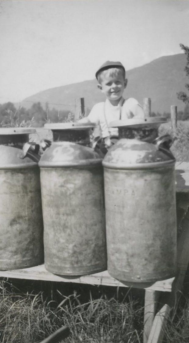 Photo en noir et blanc d'un garçon avec des bidons de lait sur un étal en bois.