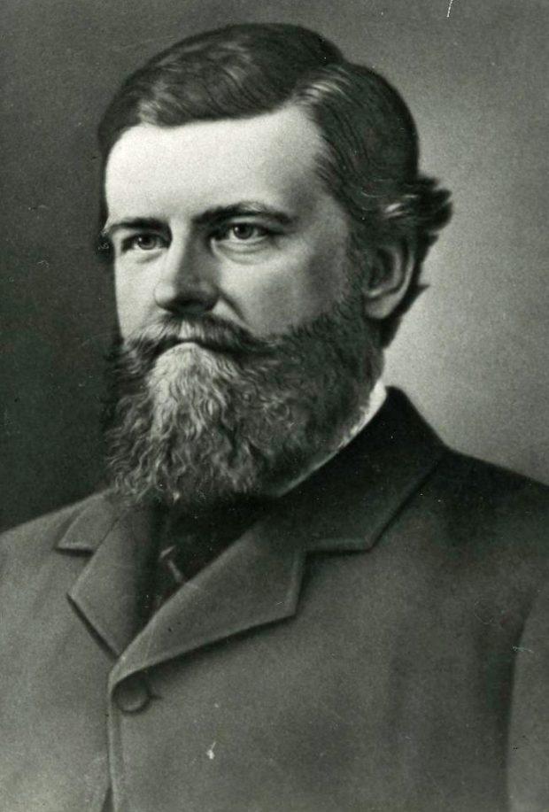 Portrait photographique en noir et blanc d'un homme aux cheveux foncés, portant une barbe et une moustache. Il est vêtu d'un habit avec une cravate.