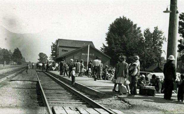 Photo en noir et blanc d'une foule de personnes sur le quai de la gare d'Agassiz.