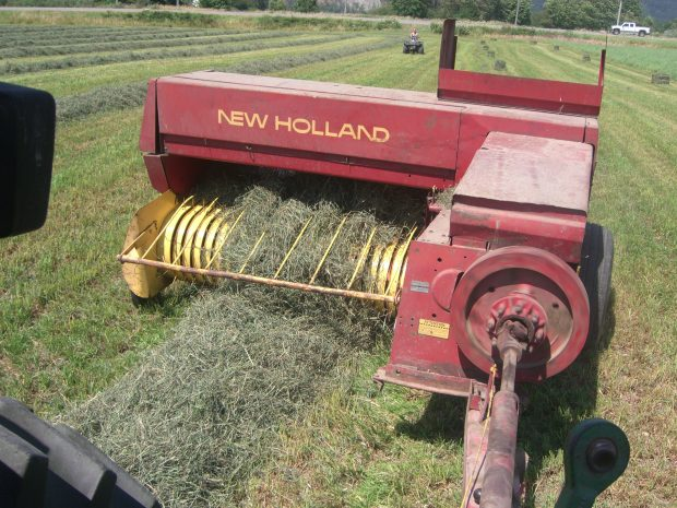 Photo en couleur d'un tracteur New Holland qui presse le foin en balles.