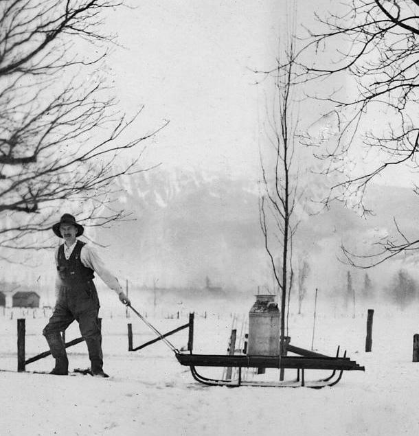 Photo en noir et blanc d'un homme tirant un bidon de lait sur un traîneau en hiver.