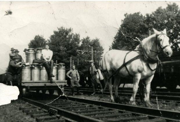 Photo en noir et blanc montrant des fermiers avec une charrette à lait chargée sur une voie ferrée. Un cheval est attelé à la charrette.