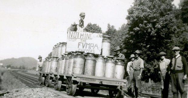Photo en noir et blanc d'agriculteurs avec un chariot à rails chargé de bidons de lait. Un homme tient un panneau qui dit : « Nothing can stop the FVMPA shippers » (Rien ne peut arrêter les expéditeurs de la FVMPA).