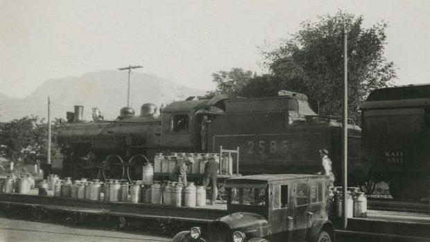 Photo en noir et blanc montrant des hommes chargeant environ 50 grands bidons de lait dans un train. Les bidons sont chargés à partir de la voiture qui se trouve devant.