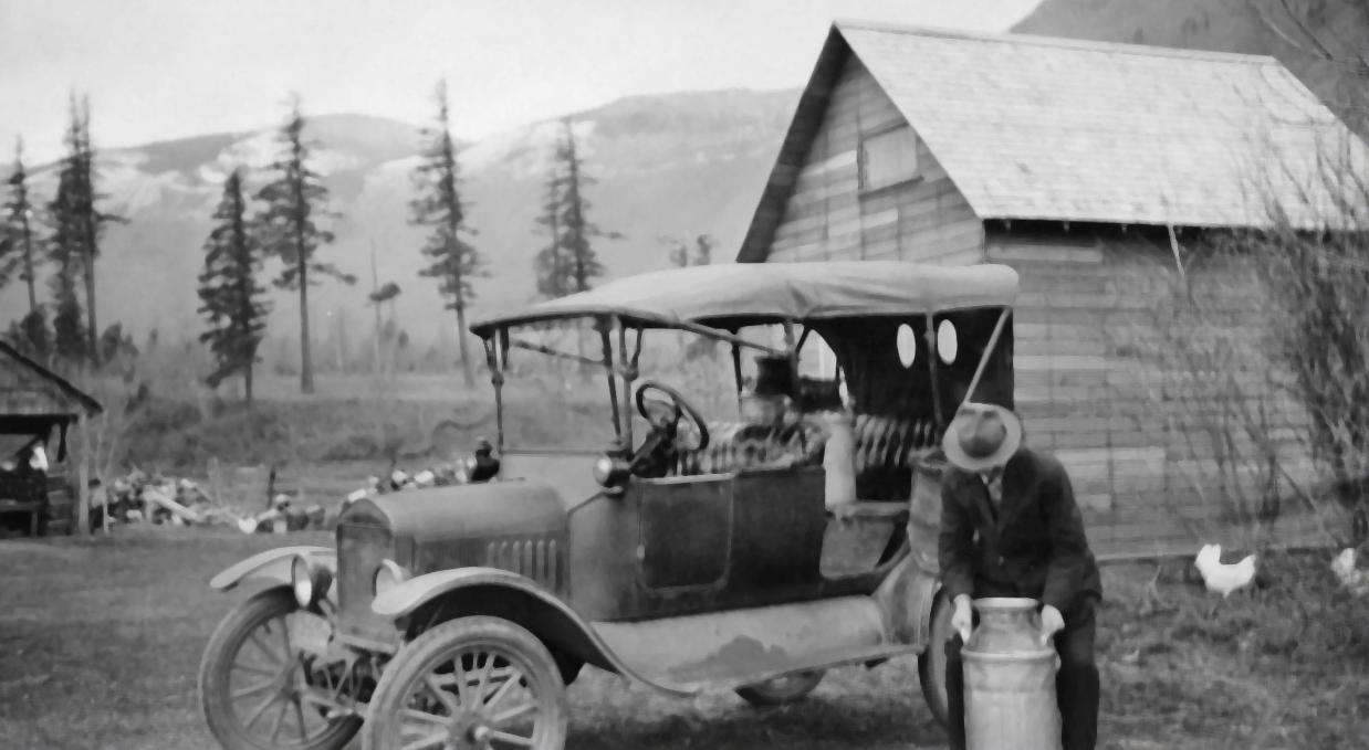 Photo en noir et blanc d'un homme chargeant des bidons de lait dans sa voiture modèle T.