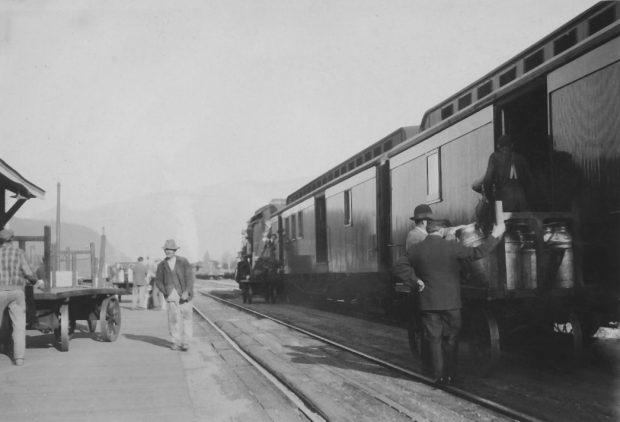 Photo en noir et blanc montrant des hommes qui chargent des bidons de lait dans un train.