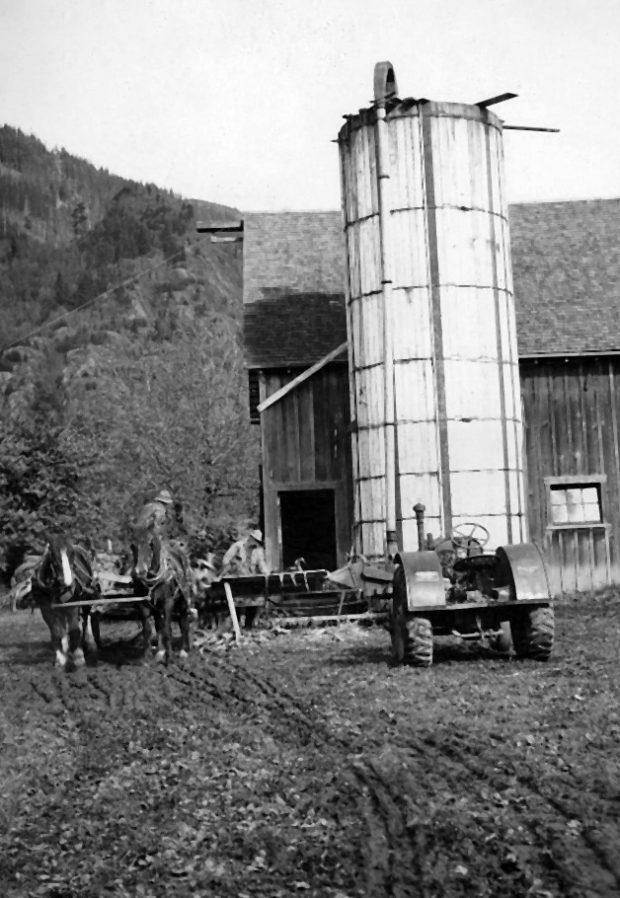Photo en noir et blanc d'une grange, d'un silo, d'un attelage de chevaux, d'un chariot et d'un tracteur.