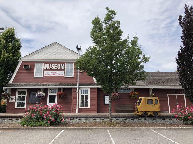 Photo en couleur d'une gare ferroviaire historique en forme de grange rouge et blanche, aujourd'hui l'Agassiz-Harrison Museum and Visitor Information Center.