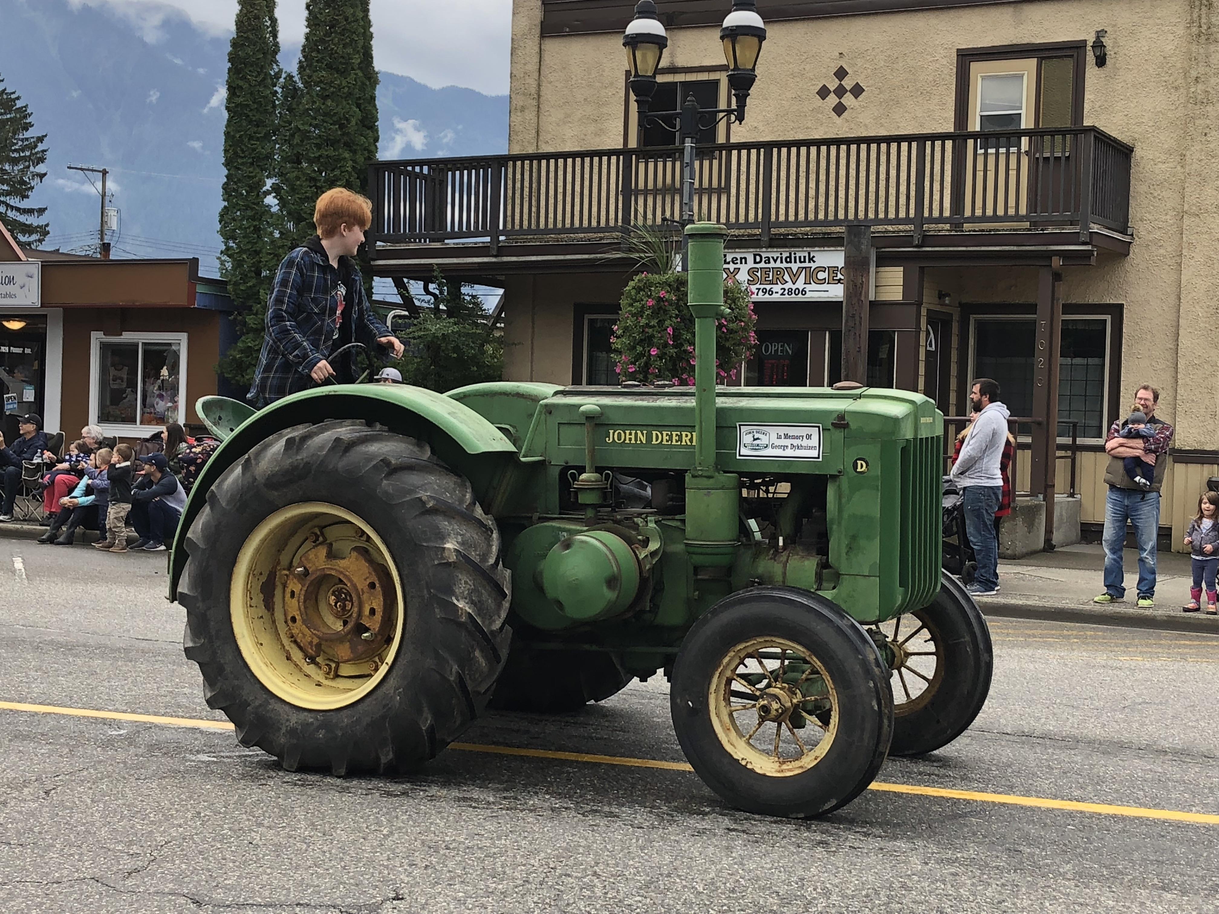 Photo en couleur d'un adolescent portant une veste à carreaux au volant d'un vieux tracteur John Deere lors d'un défilé.