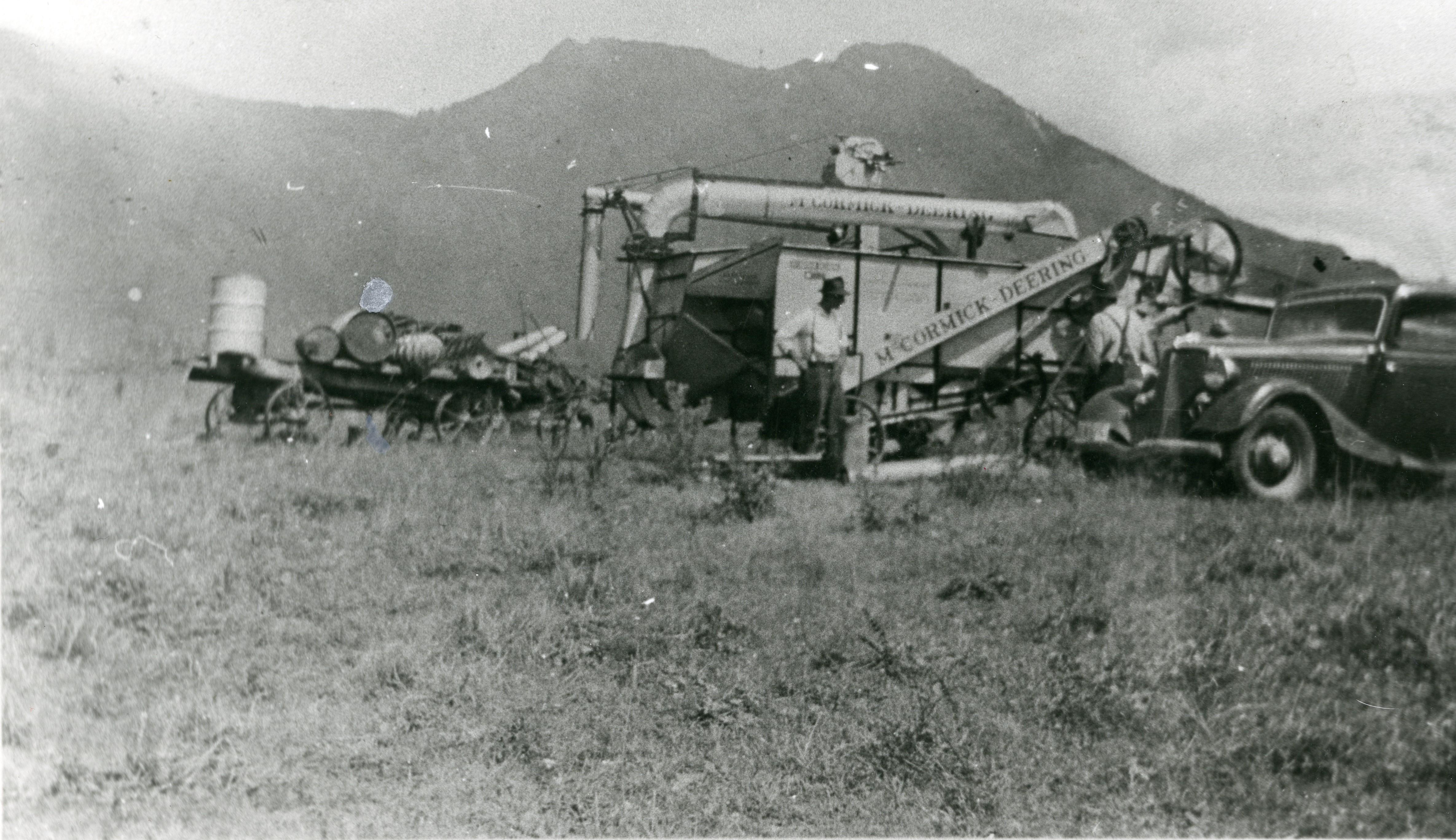 Photo en noir et blanc d'hommes travaillant dans un champ avec une batteuse McCormick-Deering. Une voiture est au premier plan et les montagnes sont en arrière-plan. Un wagon avec des barils est à côté de la batteuse.