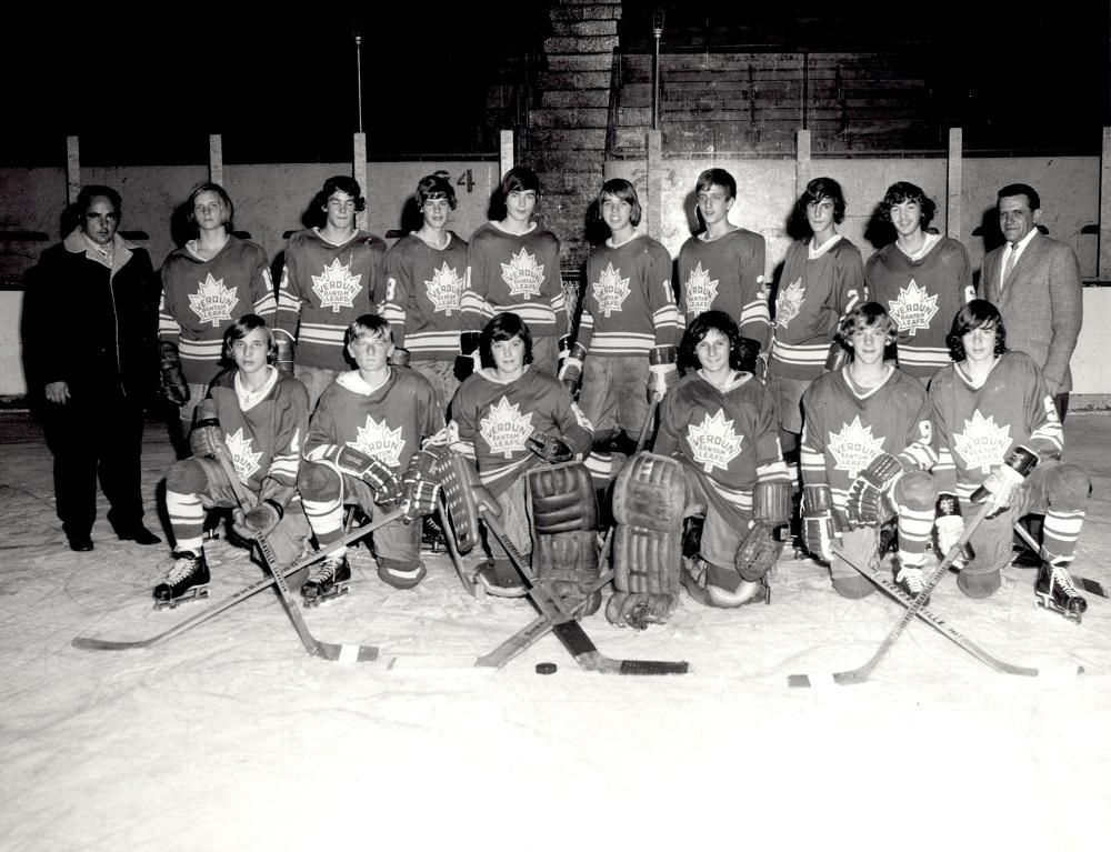 Photographie en noir et blanc sur laquelle on voit 14 garçons en tenue de hockey, dont la moitié se trouve à genoux sur une patinoire et l'autre moitié, debout derrière. Un homme se trouve de chaque côté des garçons.