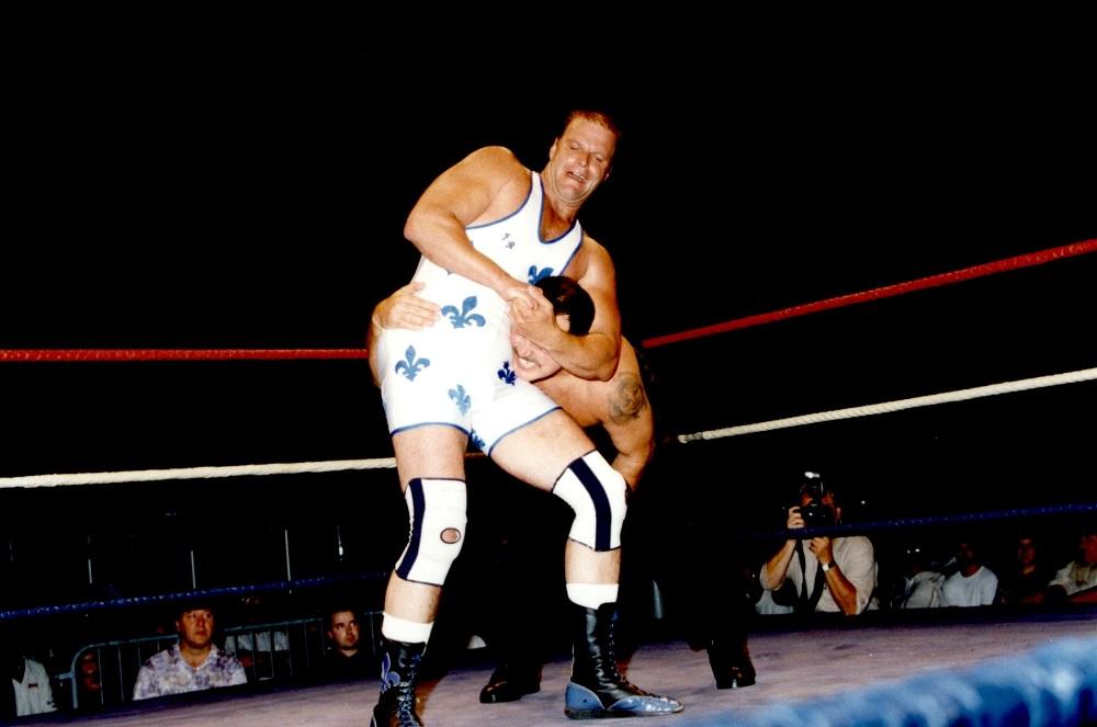 Photographie couleur où l'on voit deux hommes se battre dans une arène. Le lutteur à l'avant-plan porte un costume blanc avec des fleurs de lys bleues et des genouillères.