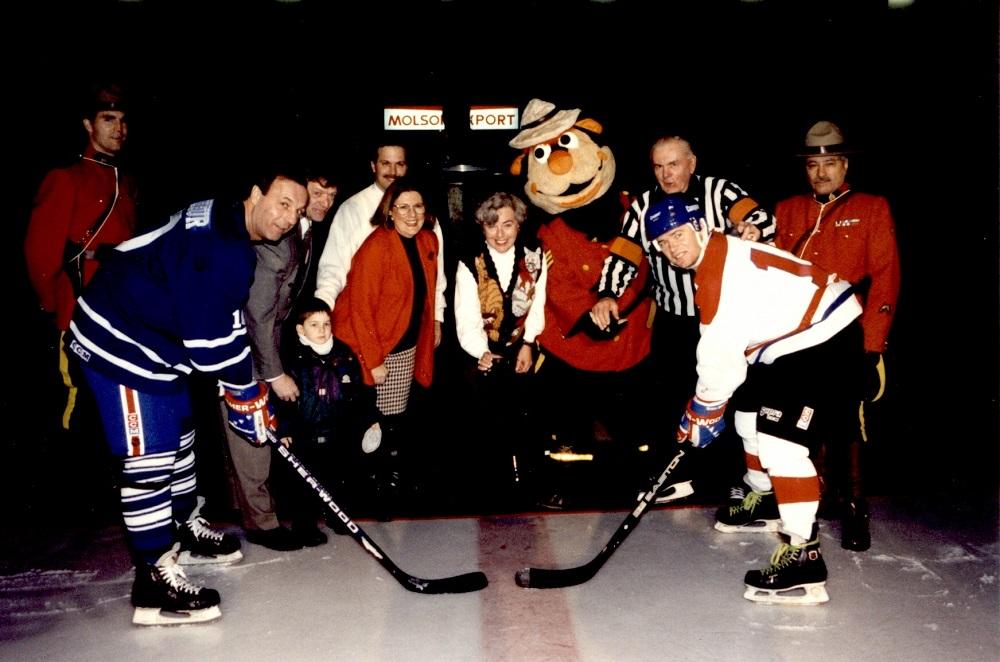 Photographie en couleurs où l'on voit deux joueurs de hockey sur une patinoire en attente d'une mise au jeu. Derrière eux se trouvent cinq personnes sur un tapis : un enfant, un homme en tenue d'arbitre, deux policiers de la Gendarmerie royale du Canada et leur mascotte.