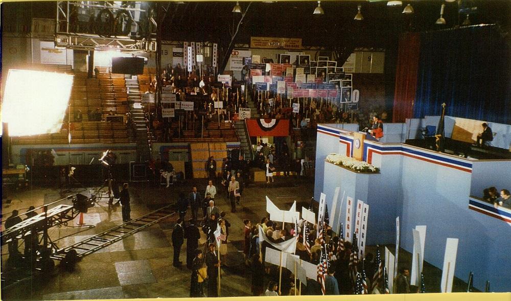 Photographie en couleurs montrant une grande tribune bleue sur laquelle se trouve une personne. Autour de cette tribune se trouvent des personnes tenant des pancartes et des caméras de cinéma.