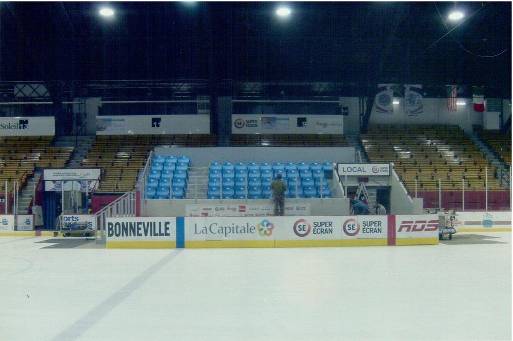 Photographie en couleurs où l'on voit à l'avant une patinoire et sa bande protectrice, sur laquelle se trouvent plusieurs noms et logos de compagnies. Au centre se trouvent plusieurs rangées de bancs de couleur bleue. Des gradins bruns et jaunes les entourent.