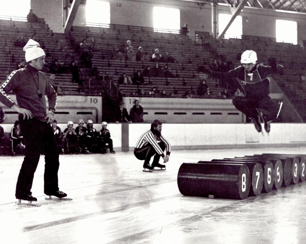 Photographie en noir et blanc où l'on voit trois hommes sur une patinoire. L'un d'eux est en train de sauter par-dessus des barils.