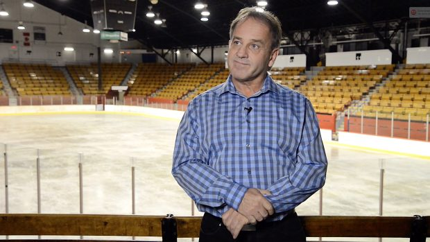 Photographie en couleurs d'un homme debout en chemise. Derrière lui se trouvent une patinoire et des gradins d'aréna.