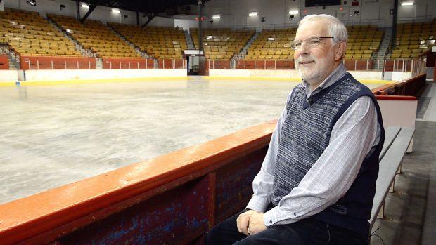 Photographie en couleurs d'un homme assis sur un banc. Derrière lui se trouvent une patinoire et des gradins d'aréna.