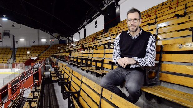 Photographie en couleurs d'un homme assis dans des gradins d'aréna.