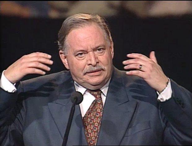 Photographie en couleurs d'un homme en complet cravate parlant à un micro.