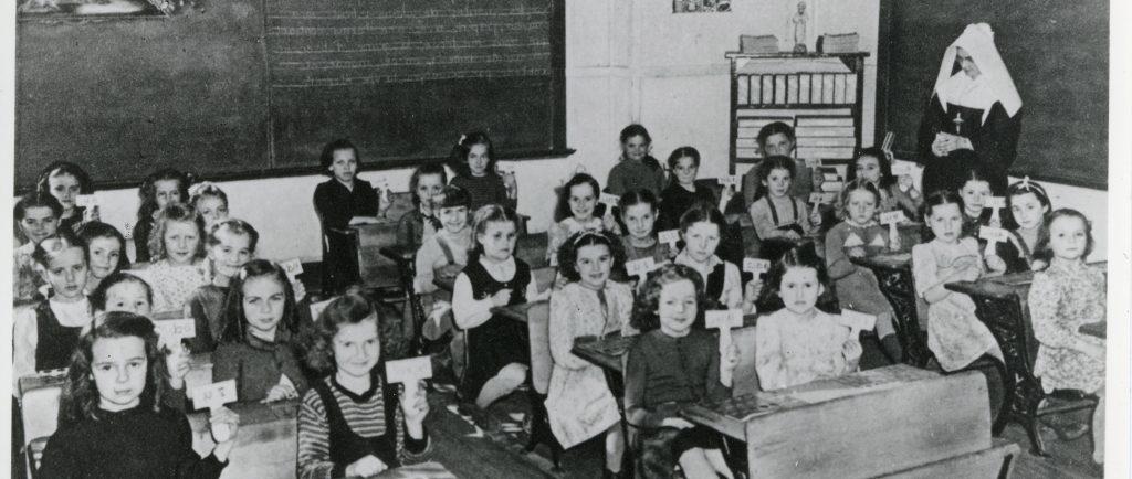 Une trentaine d'écolières assises à leur pupitre.