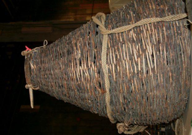 Sorte d'entonnoir fabriqué avec de petites branches, semblable à un panier tressé, appelé nasse.