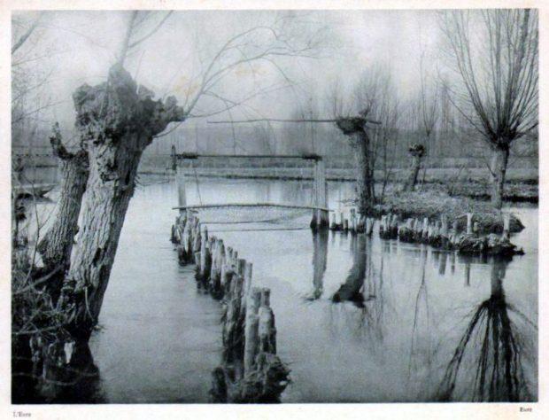 Dans un cours d'eau bordé d'arbres sans feuilles, deux rangées parallèles de poteaux courts forment un passage dont l'extrémité est fermée par un filet; photo noir et blanc.