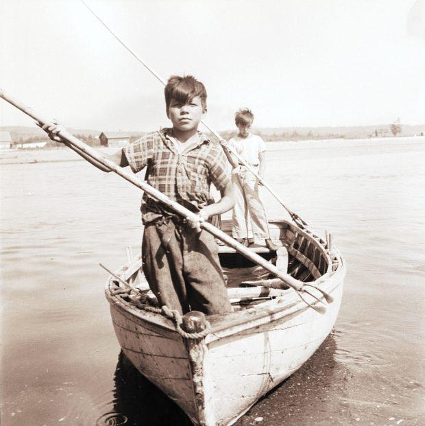 Deux garçons autochtones, face au photographe, sont debout dans une chaloupe à rames en bois près du rivage. Ils tiennent chacun une sorte de harpon ou nigogue hors de l'eau comme s'ils s'apprêtaient à piquer un poisson; photo noir et blanc.