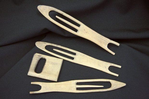 Quatre outils artisanaux en bois mince déposés sur un tissu noir : trois aiguilles en forme d'ogive pour tricoter les filets de pêche et une plaquette carrée servant de gabarit pour la taille des mailles.